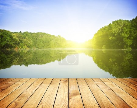 Photo for Sunset on forest lake and wooden board backgroun - Royalty Free Image
