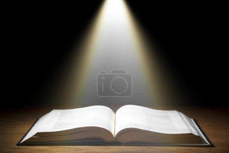 Photo pour Un vieux livre sur table en bois avec rayon de lumière - image libre de droit