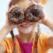 Cute kid girl eating sweet donuts...