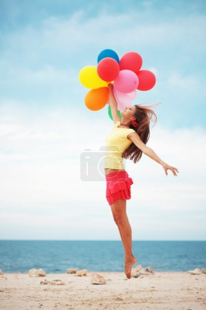 Happy girl holding bunch of colorful air balloons ...