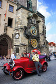 Retro car near the astronomical clock in Old Town Square waiting tourists for guided tour of the main attractions of the city on September 5, 2013 in Prague