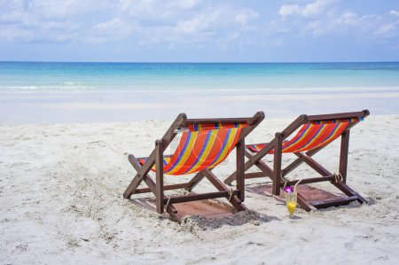 Two beach chairs on the white sand beach before blue sea on a beautiful tropical beach