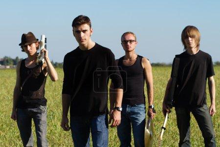 Photo pour Rockers jeunes sérieux, posant avec des instruments à l'extérieur - image libre de droit