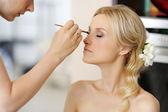Mladá krásná nevěsta použití svatební make-up