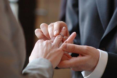 Photo pour Marié à mettre une bague de mariage sur le doigt de la mariée - image libre de droit