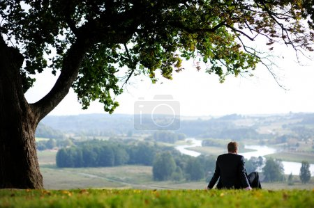 Business man resting under an oak