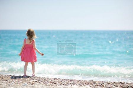 Photo pour Mignonne petite fille sur une plage de galets - image libre de droit