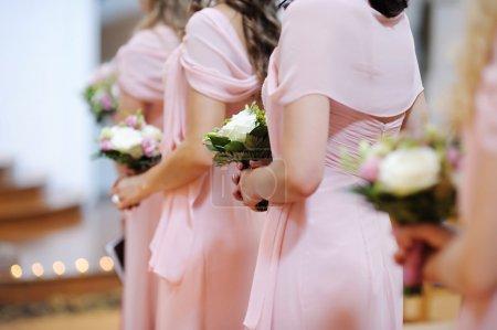 Photo pour Rangée de demoiselles d'honneur avec bouquets lors de la cérémonie de mariage - image libre de droit