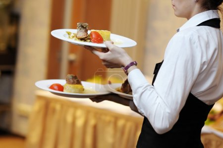 Photo for Waitress is carrying three plates with meat dish - Royalty Free Image