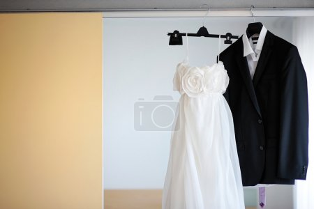 Wedding dress and a tuxedo hanging