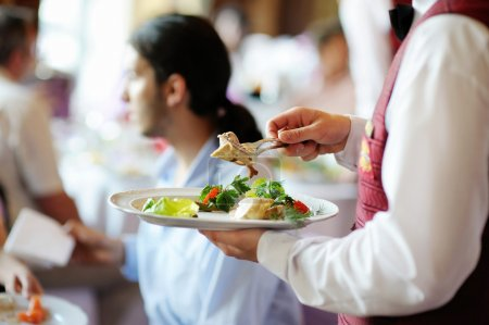 Photo for Waiter carrying a plate with meat dish - Royalty Free Image