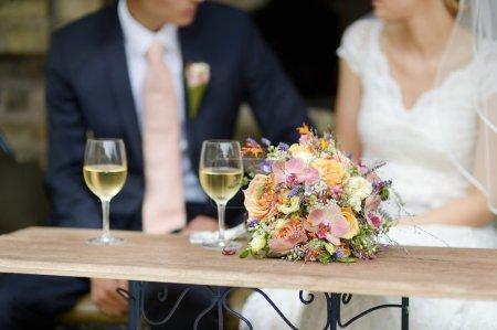 Foto de Ramo de la boda en una tabla, la novia y el novio en un fondo - Imagen libre de derechos