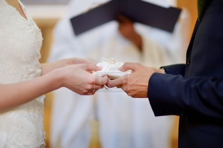 Bride and groom's hands holding wedding rings