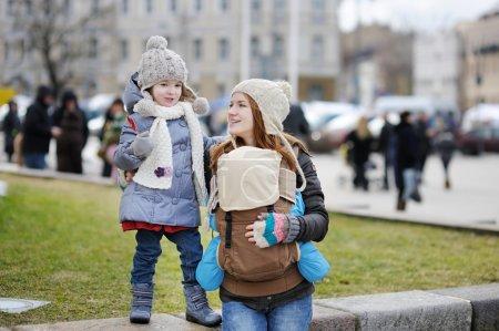 Photo pour Jeune mère et ses deux enfants au printemps - image libre de droit