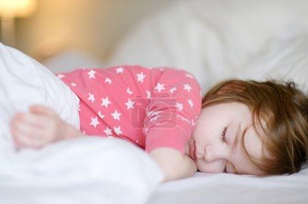 Photo pour Adorable petite fille, dormir dans un lit - image libre de droit