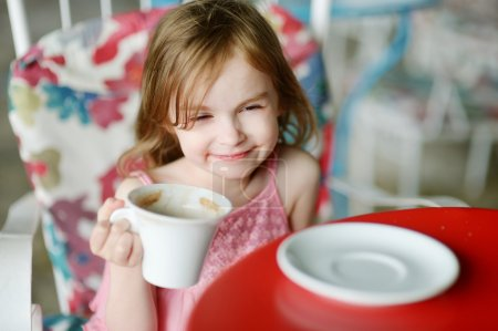 Photo for Adorable girl drinking hot chocolate in outdoor restaurant - Royalty Free Image