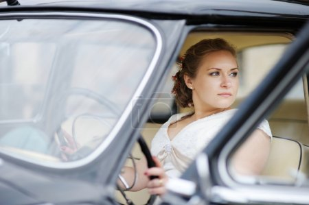 Beautiful young bride portrait in a car
