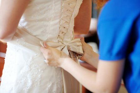 Helping the bride to put her wedding dress