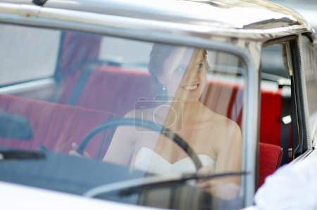 Beautiful young bride portrait in a wedding car