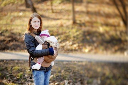 Photo pour Jeune mère et son petit bébé dans un porte-bébé - image libre de droit