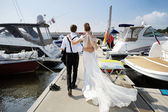 Happy bride and groom walking on pier