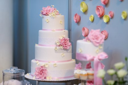 Photo for White wedding cake decorated with sugar pink flowers - Royalty Free Image