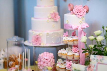 Photo pour Gâteau de mariage blanc décoré de fleurs roses - image libre de droit