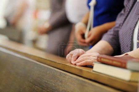 Photo pour Mains d'une femme senior tout en priant dans une église - image libre de droit