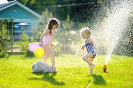 Photo pour Petites filles courant par un arroseur dans un jardin - image libre de droit