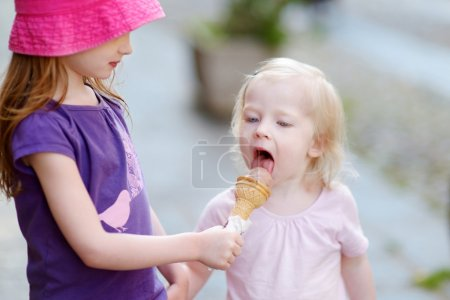 Photo pour Deux petites sœurs, manger de la crème glacée à l'extérieur - image libre de droit