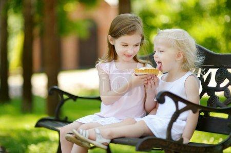 Photo pour Deux adorables petites soeurs partage crème délicieuse tarte à l'extérieur - image libre de droit