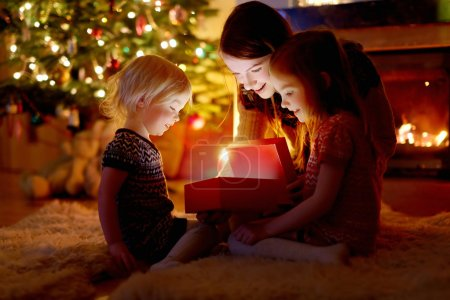 Photo for Young mother and her two little daughters with Christmas gift by a Christmas tree - Royalty Free Image