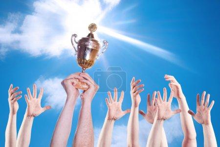 Photo pour Main de la personne avec une coupe de sport sur un fond de ciel lumineux . - image libre de droit