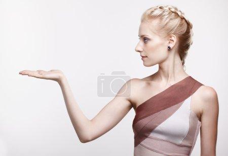Photo pour Portrait de jeune belle femme blonde posant la paume vide vers le haut, tenant petit objet imaginaire - image libre de droit