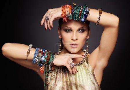 Foto de Retrato de una bella joven morena en múltiples pulseras y pendientes en color gris oscuro - Imagen libre de derechos