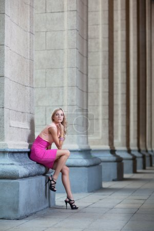 Female with pink dress against a column with high-...