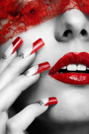 Photo pour Femme partie du visage avec les yeux fermés par un ruban rouge et avec manucure ongles acryliques français rouge - image libre de droit