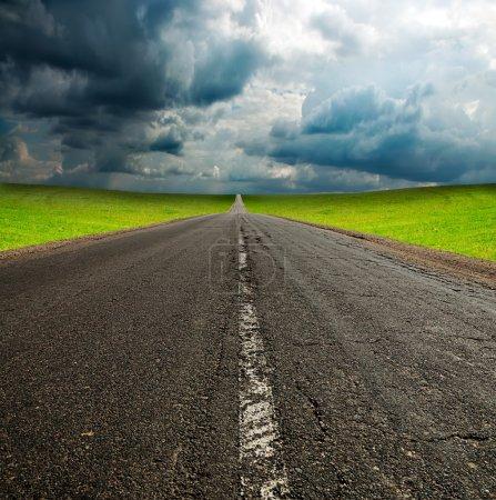 Photo pour Vieille route d'asphault cassée dans le champ vert sur ciel nuageux bleu - image libre de droit