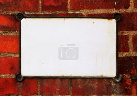Photo pour Comprimé blanc sur mur de brique rouge - image libre de droit