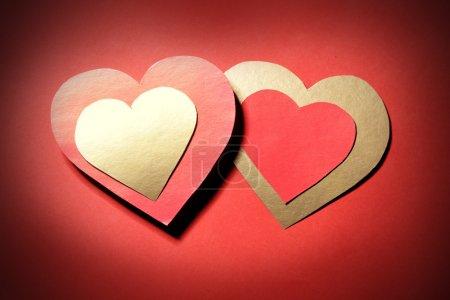 Photo pour Amour - deux coeurs en papier sur fond rouge - image libre de droit