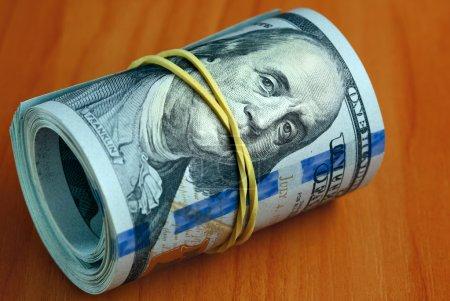 Photo pour Rouleau de billets de dollar sur une table - L'argent garder le silence concept - image libre de droit