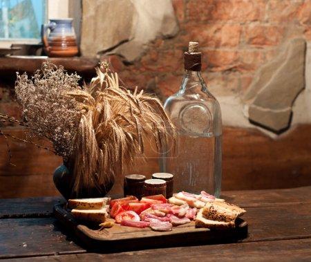 Photo pour Vodka et nourriture sur table en bois - image libre de droit