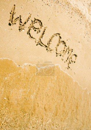 Photo pour Bienvenue écrit en une plage de sable tropicale - image libre de droit