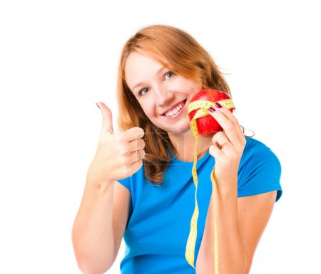 Portrait of a young sport woman holding apple and measuring tape