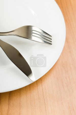 Photo for Knife and fork on white plate - Royalty Free Image