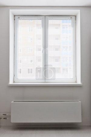 White plastic double door window with radiator under it.