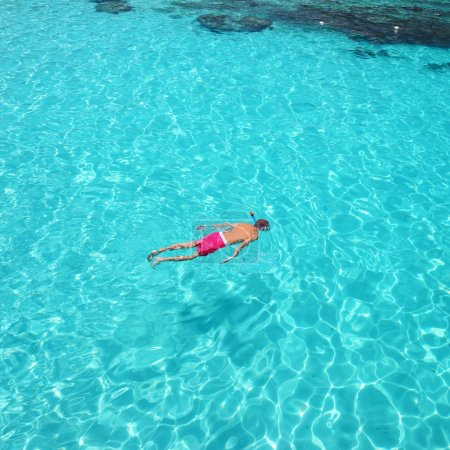 Photo for Man snorkeling in crystal clear turquoise water at tropical beach - Royalty Free Image
