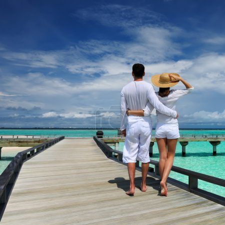 Couple on a tropical beach jetty at Maldives...