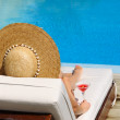 Woman in hat relaxing at the poolside with cosmopo...