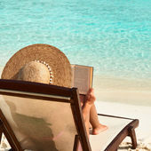 jeune femme lisant un livre à la plage